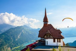 Stunning view of the top of Harder Kulm in Interlaken, Switzerland photographed in summer with paragliders flying around. Hilly Alpine landscape and Lake Thun in background. Paragliding, sunset