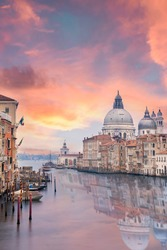 Stunning view of the Venice skyline with the Grand Canal and Basilica Santa Maria Della Salute in the distance during a dramatic sunrise. Picture taken from Ponte Dell' Accademia, Venice, Italy.