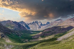 Stunning view of Tombstone Territorial Park in northern Canada during summer time from mountain peak. Stormy looking sky above.