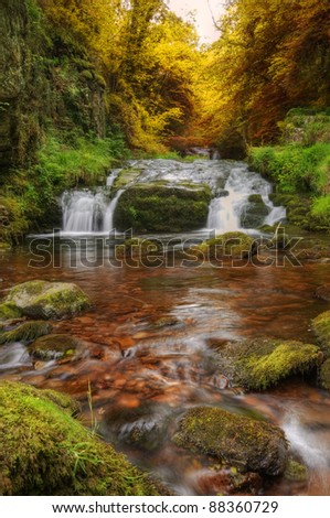 Stunning waterfall in beautiful Autumn Fall colors dense forest landscape