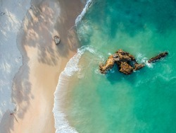Stunning wide angle aerial drone view of a rock in the water at Otama Beach near Matarangi on the Coromandel Peninsula in New Zealand. Beautiful pattern / texture of ocean and beach.