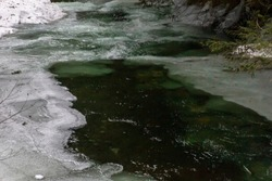 Stunning winter scene,  Whistler, British Columbia, Canada.  Green water in river merges beautifully with white ice and snow in the winter. Snow frames the deep river. River is freezing over.