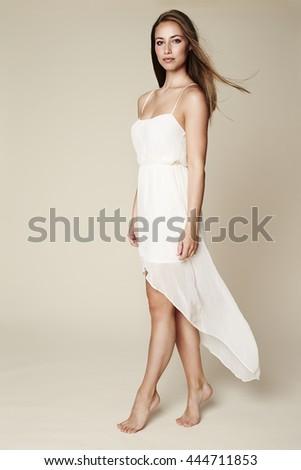 Stunning woman in white dress in studio