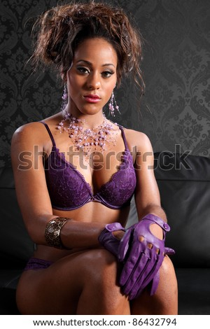 Stunning young african american glamour model woman wearing sexy purple lace lingerie and leather gloves, sitting on black leather sofa. Model has fashion necklace and bracelet on.