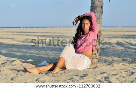 Stunning young biracial (African American and Caucasian) woman sitting on beach next to palm tree in pink sweater and sheer white skirt at sunset - stock photo
