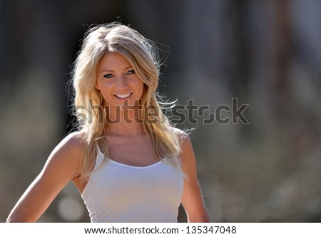 Stunning young blonde model in a white tank top and afternoon sun - country or rural portrait - copy space to right of frame
