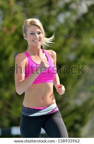 Stunning young blonde woman in pink sports bra smiling as she runs on outdoor track - fitness