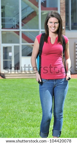 Stunning young Caucasian female student standing on campus of school wearing backpack - smiling at viewer