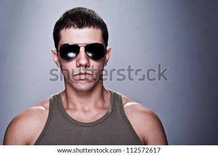 Stunning young man, with a very serious expression, appealing as the bad guy. The man is wearing sun glasses and some of his muscles are visible. A dramatic lighting has been used.