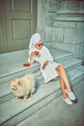 Stunning young woman in a white terry dressing gown with a white towel on her head and elegant sunglasses posing  with a cup of tea with spitz on a city street. Glamorous lifestyle. Fashion shot.