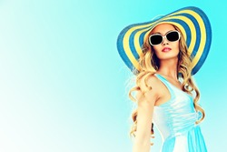 Stunning young woman in elegant hat and sunglasses posing over sky.