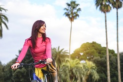 Stunning young woman in her sports outfit on a bicycle in a beautiful exotic tropical park - Beautiful smiling woman enjoying outdoor activities admiring the view