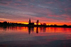 Stunningly beautiful pink and red sunset and a church in the light reflected in the lake, Russia