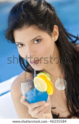 Stunningly beautiful young Latina Hispanic woman in drinking a cocktail by a blue swimming pool