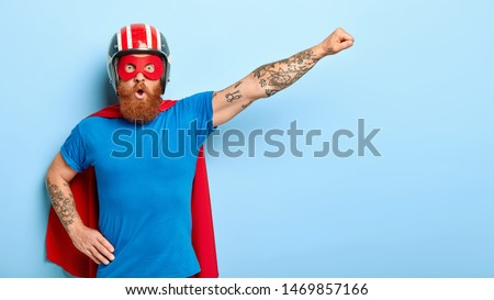 Stupefied emotive man with ginger beard being cartoon character, keeps arm in flying gesture, wears protective headgear, blue t shirt and red cloak, has shocked expression, saves our universe
