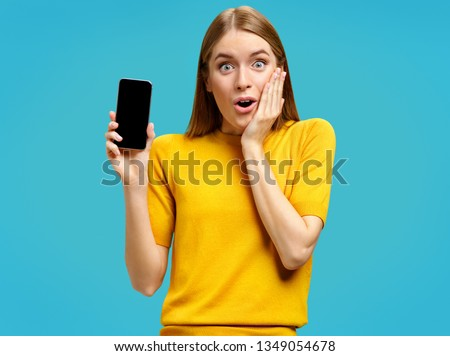 Stupefied girl opens eyes and mouth widely, holds a phone. Photo of young girl with surprised expression in yellow sweater on blue background. Omg concept