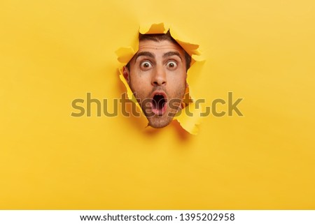 Stupefied young man with bristle keeps jaw dropped from surprisement, has popped eyes, stares through yellow torn paper, impressed by shocking rumors. People, human emotions and reaction concept