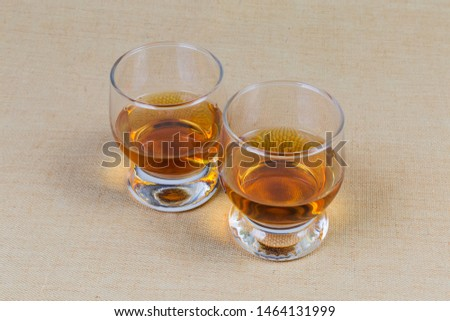 sTwo portion of brandy in brandy bowls on a textile surface  #1464131999