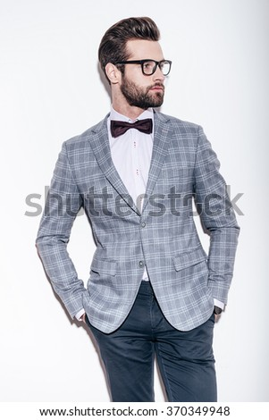 Style and intelligence. Handsome young man wearing suit and glasses keeping hands in pockets and looking away while standing against white background
