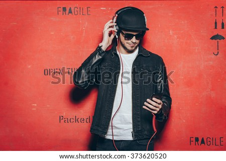 Style and music. Handsome young man adjusting his headphones and looking at his smart phone while standing against red background