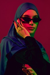 Style. Beautiful arab woman in stylish hijab isolated on burgundy studio background in neon light with copyspace for ad. Fashion, beauty, style concept. Female model with trendy make up, accessories.