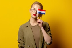 Style blonde woman in jacket with Dutch flag on yellow background