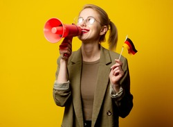 Style blonde woman in jacket with German flag and megaphone on yellow background