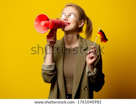 Style blonde woman in jacket with German flag and megaphone on yellow background Foto d'archivio ©