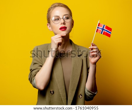 Style blonde woman in jacket with Norwegian flag on yellow background