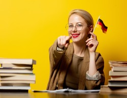 Style blonde woman sitting at table with books and flag of Germany on yellow background