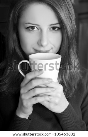 Style girl drinking coffee near wood doors. Photo in black and white style.