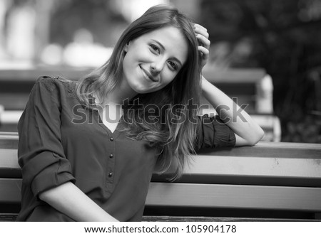 Style girl sitting on the bench in the cafe. Photo in black and white style.