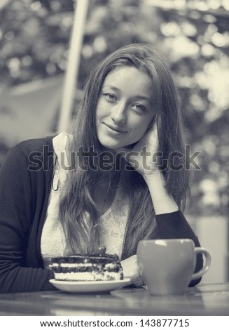 Style girl with cake and cup sitting in the cafe. Photo in black and white style.