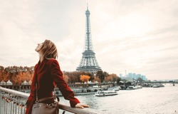 Style redhead girl in red coat and bag at parisian street with view at Eiffel tower in autumn season time