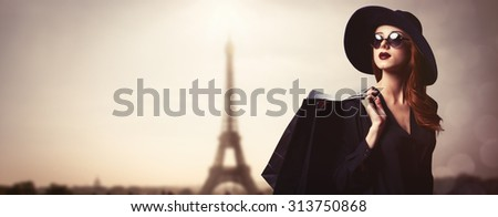 Style redhead girl with sunglasses and shopping bags on Eiffel tower background.