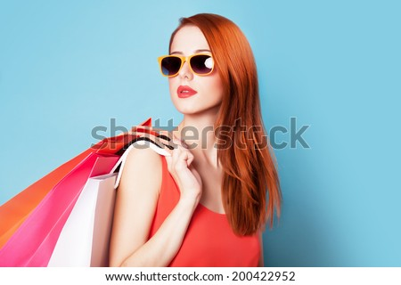 Style redhead women holding shopping bags on blue background.