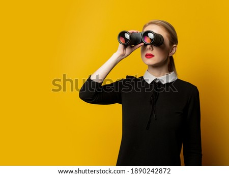 Style woman in black formal clothes with binocular on yellow background Stock photo ©
