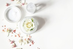 Styled beauty composition. Skin cream, shampoo bottle, dry flowers, rose and Himalayan salt. White table background. Organic cosmetics, spa concept. Empty space, flat lay, top view, web banner.