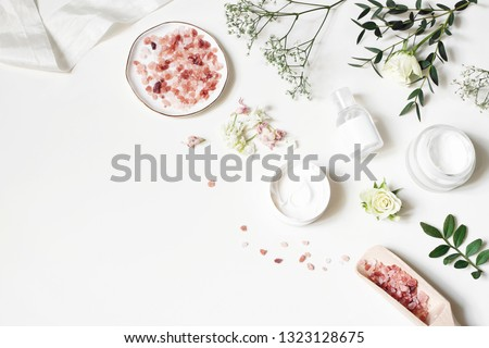 Styled beauty corner, web banner. Skin cream, tonicum bottle, dry flowers, leaves, rose and Himalayan salt. White table background. Organic cosmetics, spa concept. Empty space, flat lay, top view.