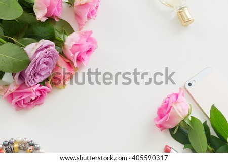 Styled desktop scene  with  mobile and flowers, copy space on white table