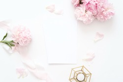 Styled feminine top view.on white background with wedding card, pink peonies petals, candle