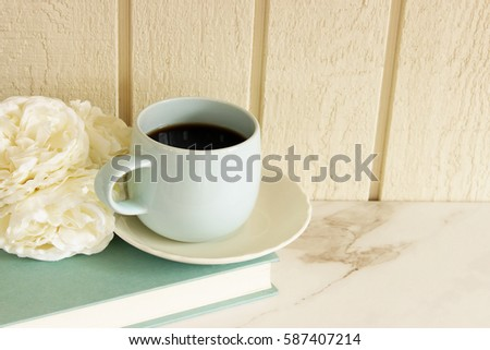 Styled home interior blank wall scene with coffee, flowers and book with soft blue accents. Room for copy. #587407214