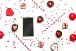 Styled photo of St. Valentine's Day flatlay top view isolated on white. Red heart sweets, gifts in craft paper, proposal ring in box, smartphone mockup, candles and confetti.