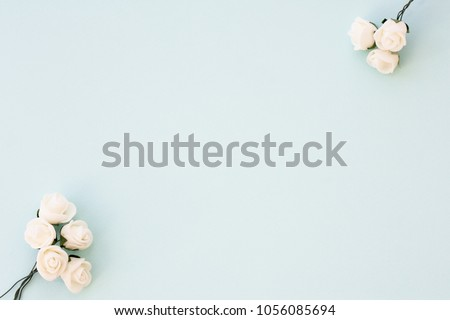 Styled stock photo. Feminine wedding desktop mockup. White roses on delicate blue background. Copy space. Top view. Picture for blog