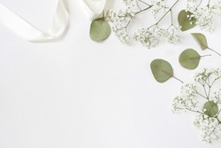 Styled stock photo. Feminine wedding desktop mockup with baby's breath Gypsophila flowers, dry green eucalyptus leaves, satin ribbon and white background. Empty space. Top view. Picture for blog.