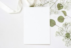 Styled stock photo. Feminine wedding desktop stationery mockup with blank greeting card, baby's breath Gypsophila flowers, dry green eucalyptus leaves, satin ribbon and white background. Empty space.