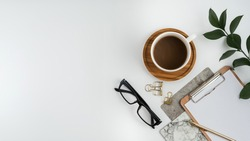 Styled stock photography white office desk table with blank notebook, computer, supplies and coffee cup. Top view with copy space. Flat lay.