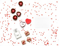 Styled Valentine's Day flatlay top view isolated on white. Sweet hearts, gifts in craft paper, proposal ring in box, perfume, empty note and confetti. Party invitation or web ad template
