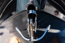 Stylised shot of a bow anchor, made of highly polished stainless steel protruding from the bow of a sports boat. The anchor is the only aspect in focus, the rest is blurred for effect.