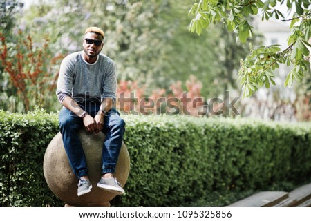 d261153108d Stylish african american boy on gray sweater and black sunglasses posed on  street. Fashionable black
